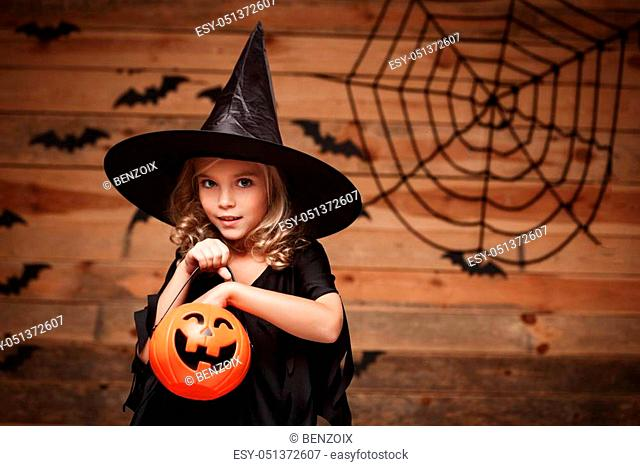 Halloween Witch concept - little caucasian witch child enjoy with halloween candy pumpkin jar. over bat and spider web background