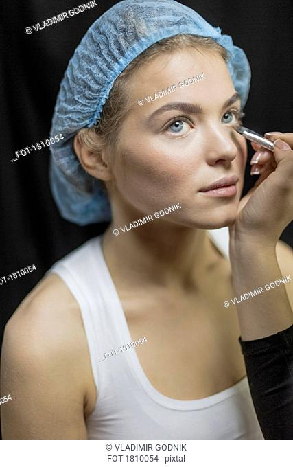 Makeup artist applying makeup to eyes of young woman in shower cap
