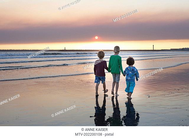 Rear view of three kids walking on the beach during sunset, Viana do Castelo, Norte Region, Portugal