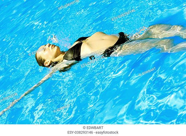 woman takes a sunbath in the swimming pool