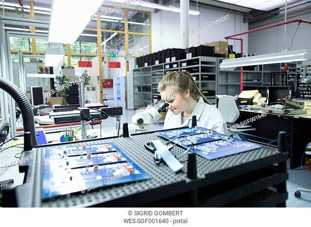 Technician examining circuit board with microscope