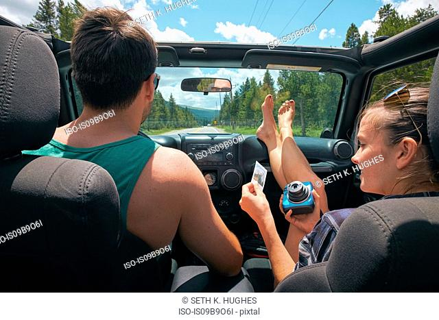 Young woman with boyfriend on road trip holding instant photograph, Breckenridge, Colorado, USA
