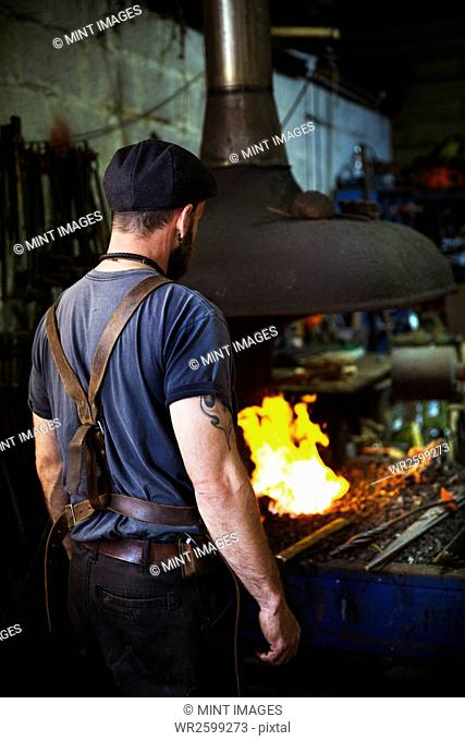 A blacksmith wearing a leather apron stands in front of a furnace in a workshop