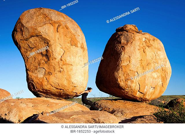 Woman holding a rock, Devils Marbles, Northern Territory, Australia
