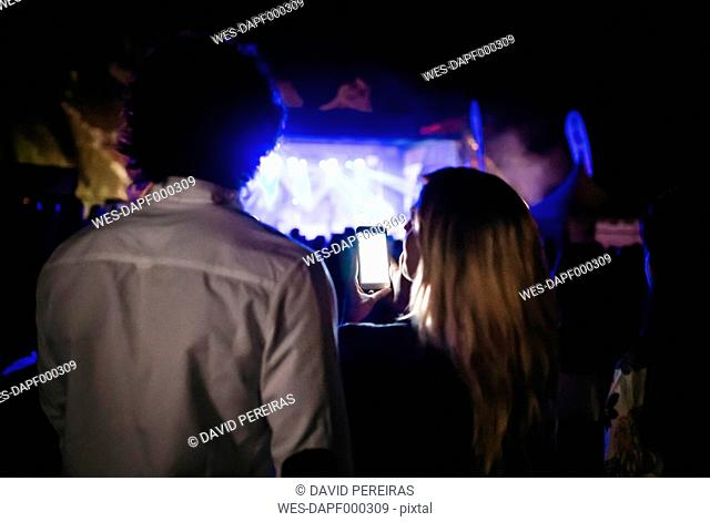 Back view of young woman taking pictures with smartphone at summer concert