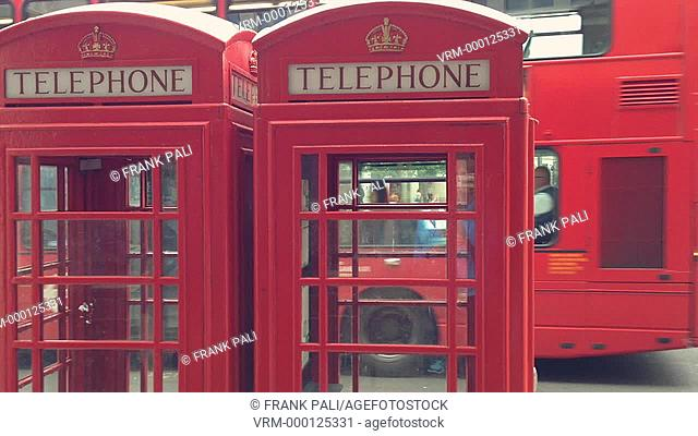 The Iconic red phone booth in London with buses going by