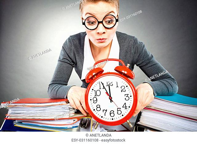 Corporate job workaholism time concept. Emotional secretary with clock. Nervous female office worker at desk with alarm ringer