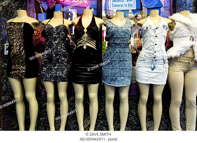 Row of six female dummies on sidewalk wearing mini dresses
