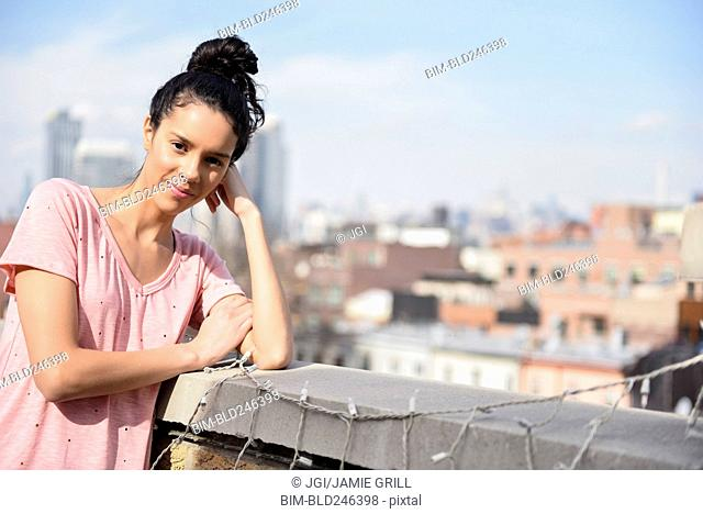 Hispanic woman leaning on rooftop near string lights