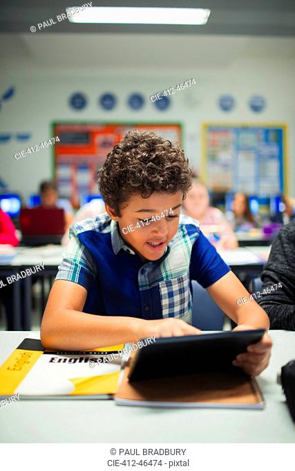 Junior high school boy student using digital tablet in classroom