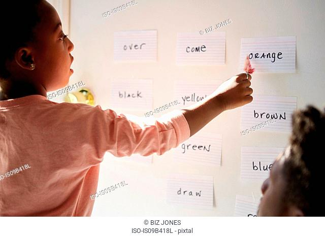 Girl with father pointing at words on wall