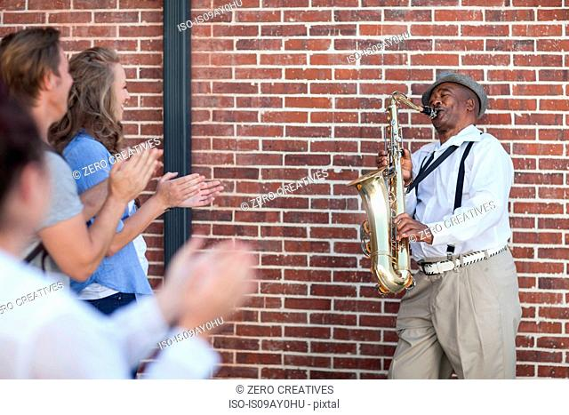 Street musician, playing saxophone, entertaining pedestrians, pedestrians clapping