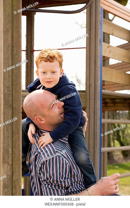 Father carrying son on playground
