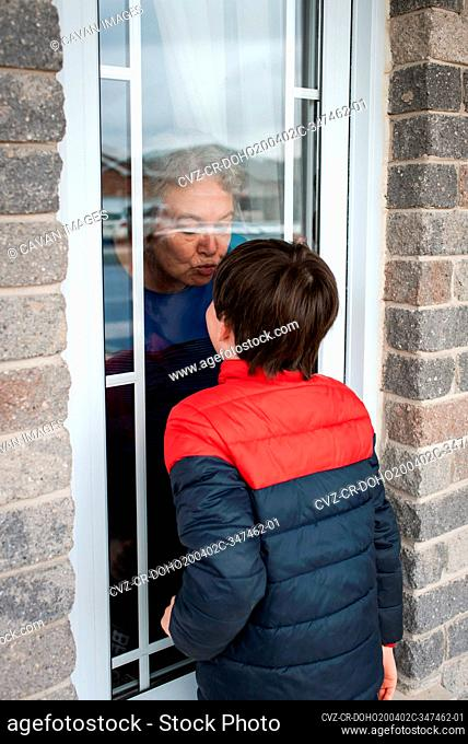 Young boy looking through window at grandma during Covid 19 pandemic