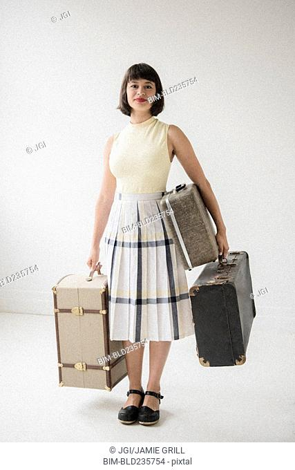 Portrait of smiling Hispanic woman holding suitcases