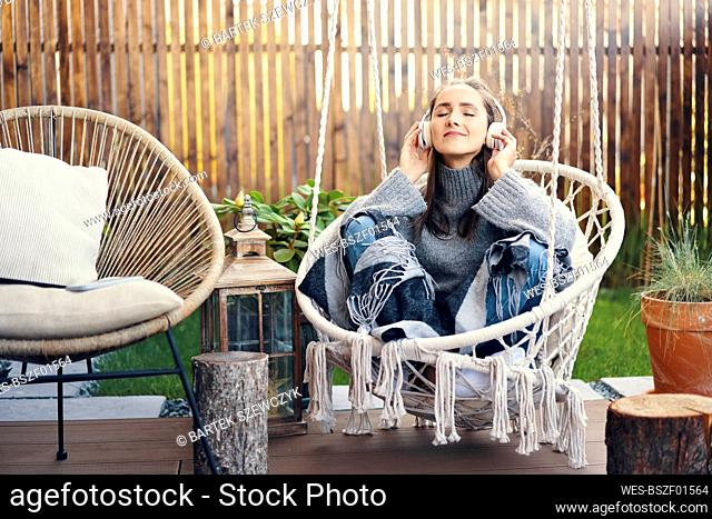 Smiling woman with eyes closed listening music while relaxing on swing in yard