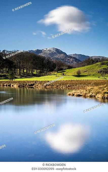 A single cloud over a snow capped mountain reflected in the river Brathay