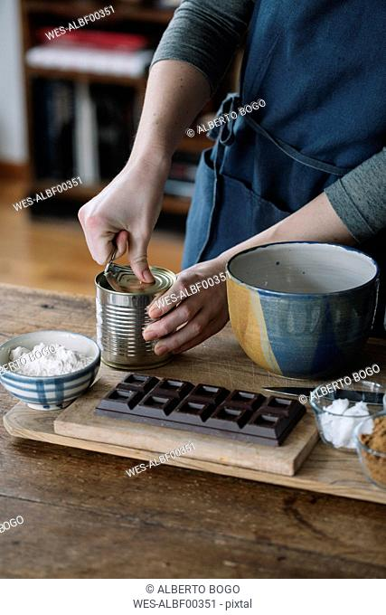 Woman opening preserve can for preparing batter for homemade vegan chickpea cookies, partial view