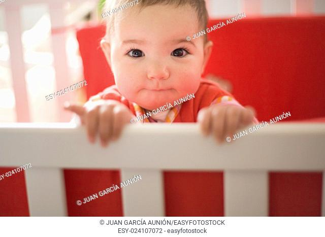 Little baby girl with beautiful dark eyes standing at white crib and playing just after awakening
