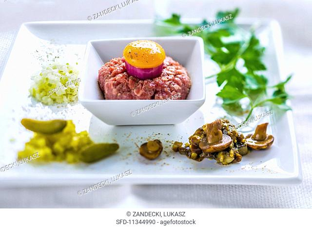 Beef tartare with red onion, egg yolk and sides