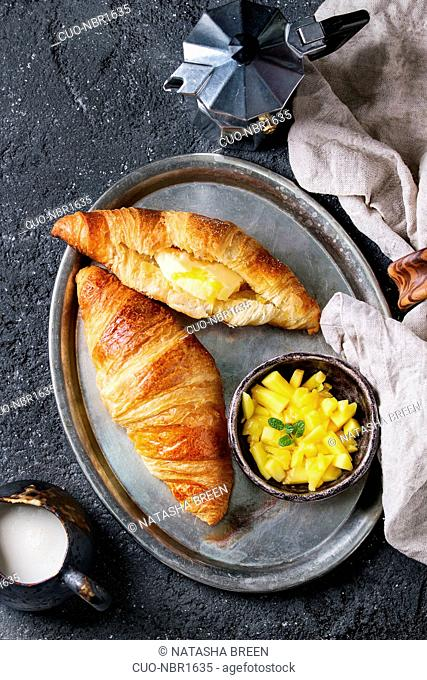 Breakfast with two croissant, butter, coffee maker, cream and sliced mango fruit, served on serving metal tray with textile napkin over black concrete texture...