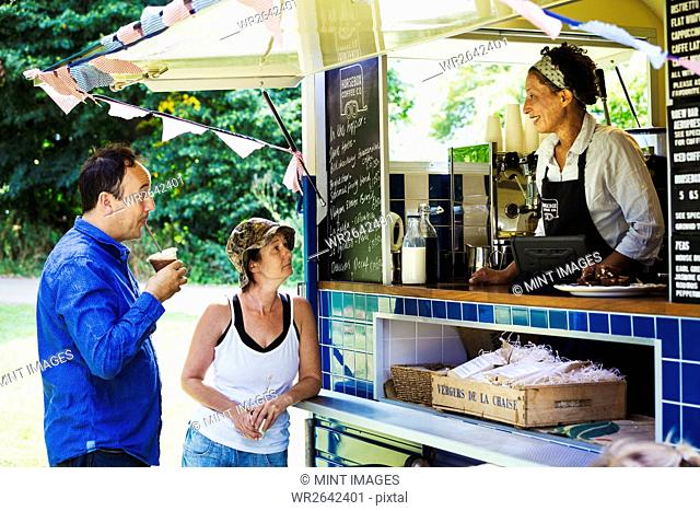 Man and woman standing at the counter of a mobile coffee shop