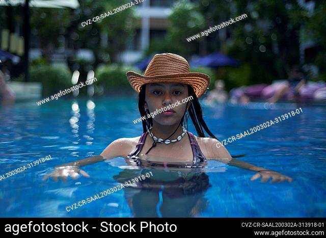 Stylish trendy young teen visco girl in the pool wearing a straw hat