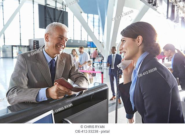 Customer service representative helping businessman with passport at airport check-in counter