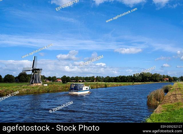Boat sails along the Tjongermill windmill near Mildam in the Dutch province Friesland