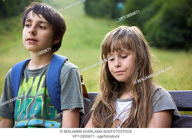 bored young girl with her brother sitting on bench in nature