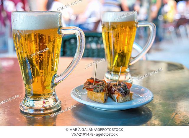 Spanish aperitif: two glasses of beer with tapa on a terrace. Madrid, Spain