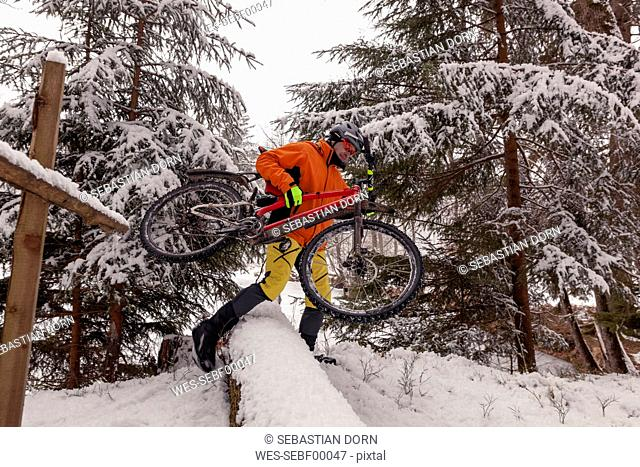 Man with mountainbike crossing fallen tree on path in winter forest
