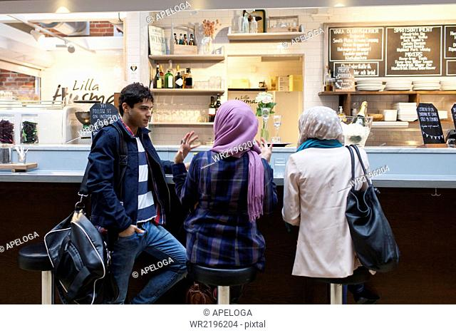 Friends talking at cafe counter in railroad station