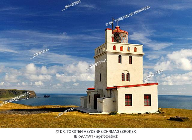 Kap Dyrhólaey Lighthouse, to the east the Reynisdrangar, the black rock needles near Vik, South Coast, Iceland, Europe