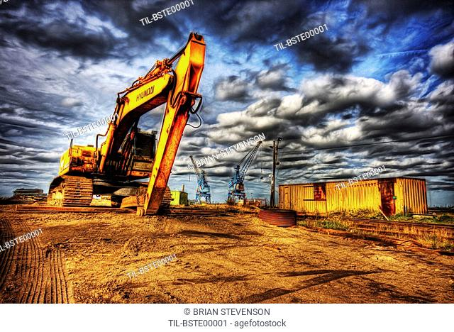 A large yellow digger with caterpillar tracks on a building site with cranes in the distance and ominous dark clouds below a blue sky