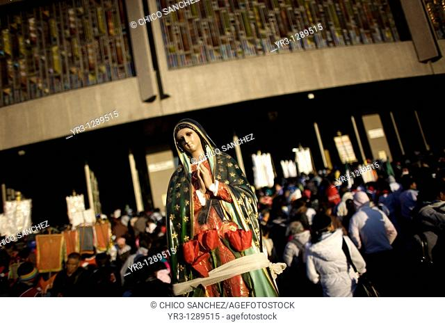 A pilgrim carries a statue of the Our Lady of Guadalupe outside the Our Lady of Guadalupe Basilica in Mexico City, December 11