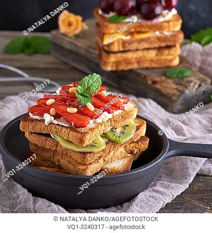 French toast from white bread with cottage cheese, strawberries, kiwi in a black cast-iron round frying pan with a handle on a gray wooden table