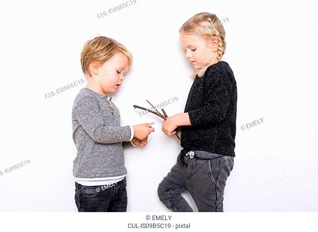 Young girl and boy leaning against white background, girl holding twigs