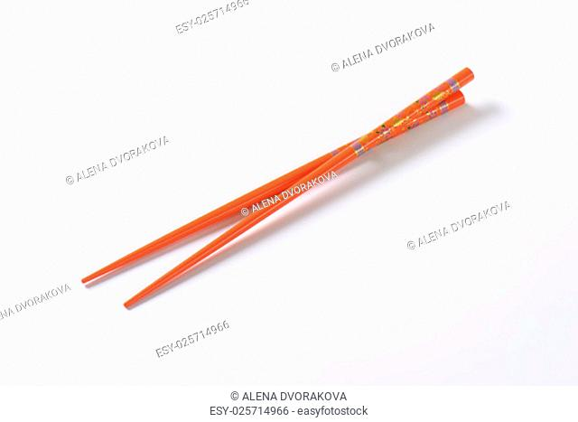 pair of orange chopsticks on white background
