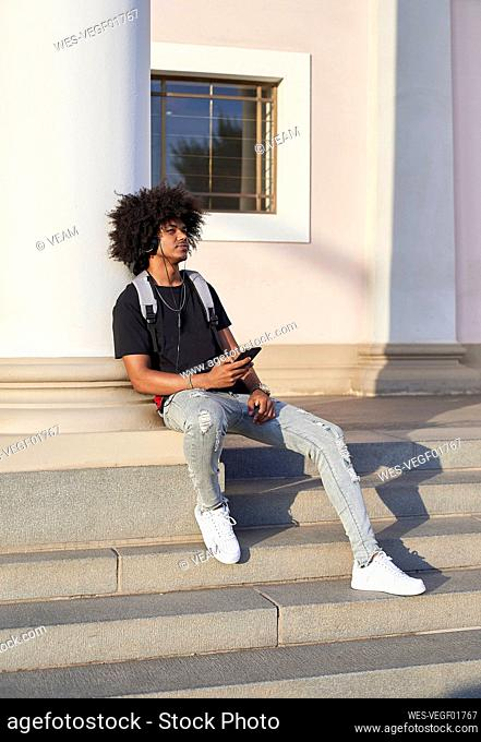 Young man listening to music and holding his smartphone, sitting on steps