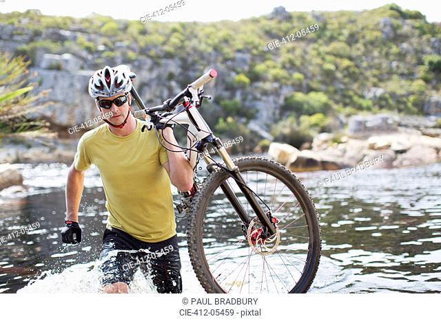 Man carrying mountain bike in river