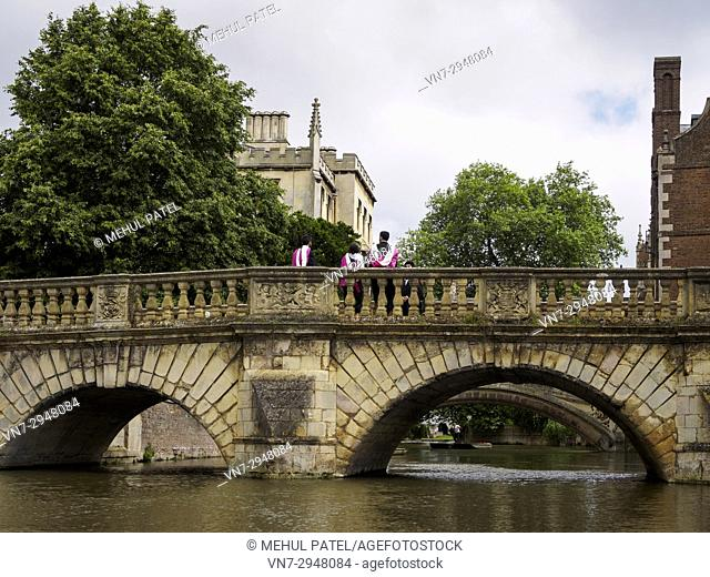 Graduates from St John's College, University of Cambridge, in ceremonial attire on a bridge over the river Cam, Cambridge, England, UK