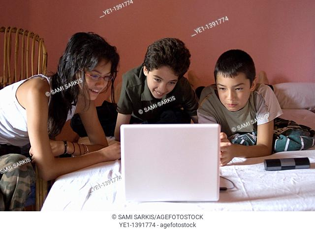 Three children lying on a bed using a laptop, France