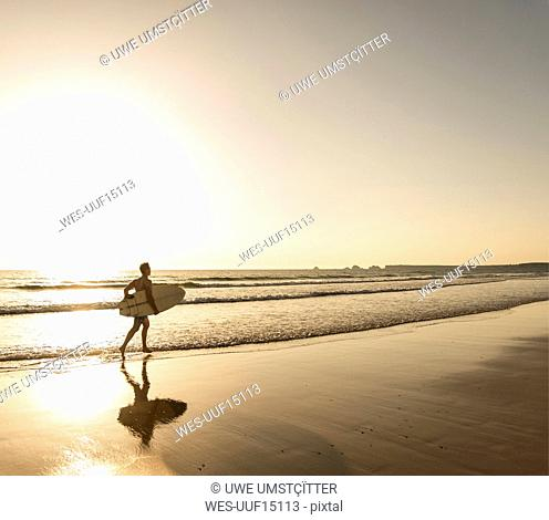 Young man running on beach, carrying surfboard
