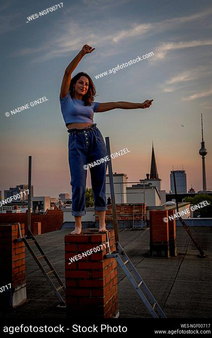 Happy woman with arms raised standing on brick wall against sky during sunset