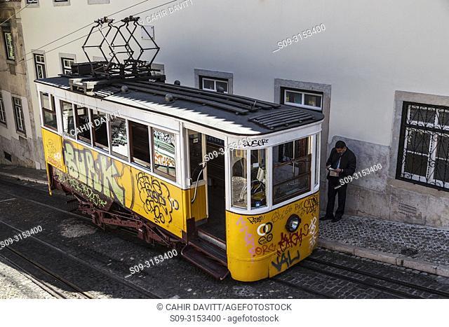 A grafitti covered, yellow Bica Funicular electric train at the upper terminus of the Elavador da Bica, on Calcada da Gloria Street, Sao Paulo, Lisbon, Lisboa