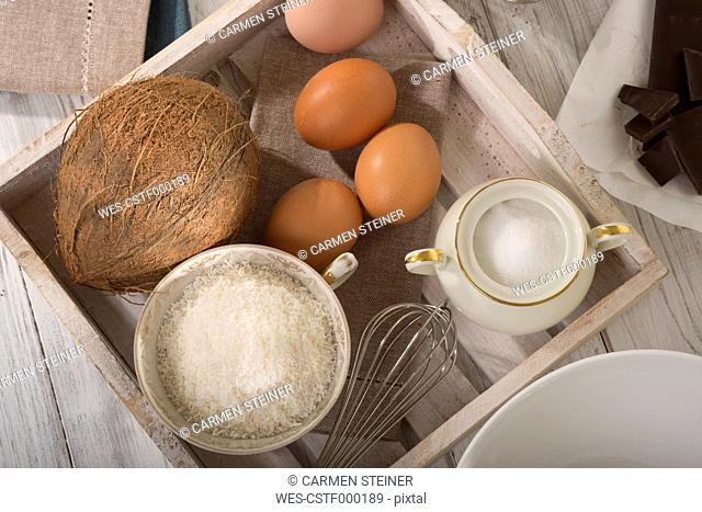 Ingredients of coco macaroons on wooden tray, elevated view