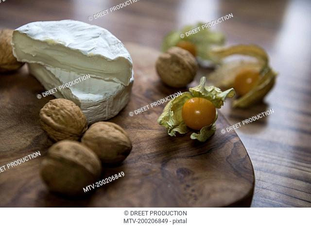 Close up of two halves of cheese and walnuts with a Cape Gooseberry, Germany