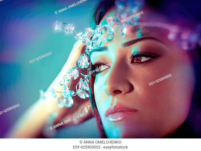Closeup portrait of gorgeous woman with perfect makeup wearing luxury diamonds wreath over blue background, stylish look for Christmas party