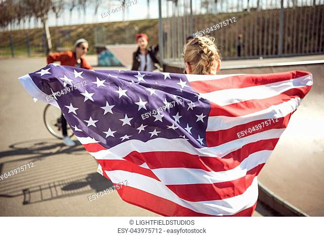 Back view of young girl standing with american flag and looking at friends at skateboard park